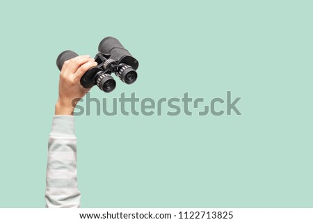 Woman with binoculars on green background, looking through binoculars, journey, find and search concept. Royalty-Free Stock Photo #1122713825