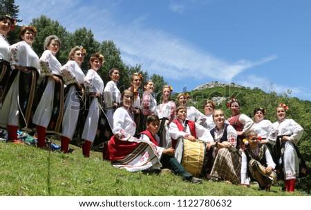 Vratsa, Bulgaria - June 24, 2018: People in traditional authentic folklore costume a meadow near Vratsa, Bulgaria #1122780632