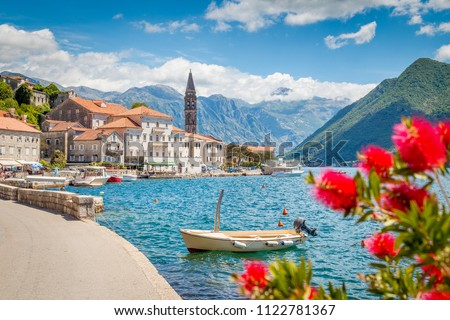 Scenic panorama view of the historic town of Perast at famous Bay of Kotor with blooming flowers on a beautiful sunny day with blue sky and clouds in summer, Montenegro, southern Europe #1122781367