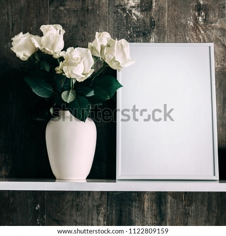 Front view of an empty photo frame layout and a bouquet of white roses in a vase. White flowers on a wooden shelf in the background of vintage wall. square
