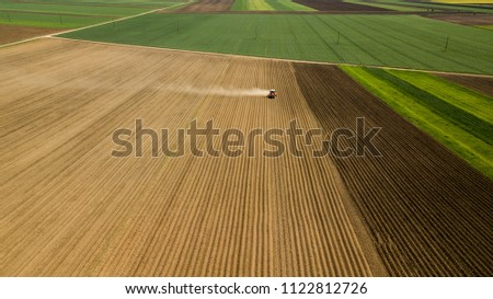 Farmer with a tractor on the agricultural field sowing. tractor working on the agricultural field in spring. aerial view by drone	  #1122812726