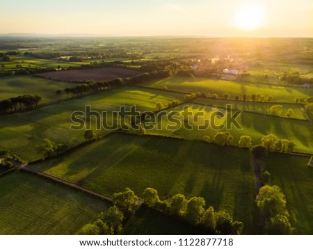 Aerial view of endless lush pastures and farmlands of Ireland. Beautiful Irish countryside with emerald green fields and meadows. Rural landscape on sunset. #1122877718