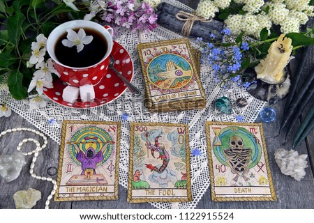Tarot cards with cup of tea, flowers and black candles on planks. Occult, esoteric and divination still life. Halloween background with vintage objects and magic ritual #1122915524