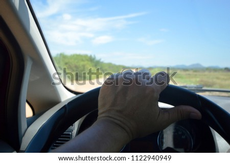 human hand holding a steering wheel while driving on a dirt road #1122940949