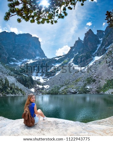 Smiling girl sitting  by Emerald Lake on the rock on hiking trip in beautiful mountains. Rocky Mountain National Park, close to Estates Park, Colorado, USA. #1122943775