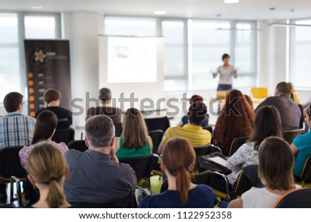 Business and entrepreneurship symposium. Speaker giving a talk at business meeting. Audience in conference hall. Rear view of unrecognized participant in audience. #1122952358