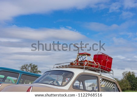 travel case on roof of oldtimer with tricycle at rural countryside south germany springtime near city stuttgart #1122968516