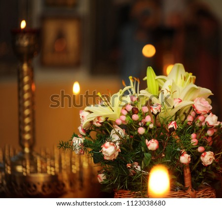 basket with flowers and candles in the church #1123038680