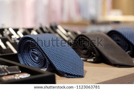 Selective focus at blue necktie. Roll up necktie on the table and blur background . Concept of gentleman and necktie fashion. Shopping , father's day. #1123063781