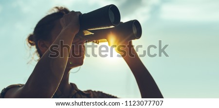 Beautiful Young Woman Looking Through Binoculars At The Sea On A Bright Sunny Day Royalty-Free Stock Photo #1123077707