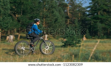 Fat bike also called fatbike or fat-tire bike in summer riding in the forest. The guy rides a bicycle among trees and stumps. He overcomes some obstacles on a bumpy road. #1123082309