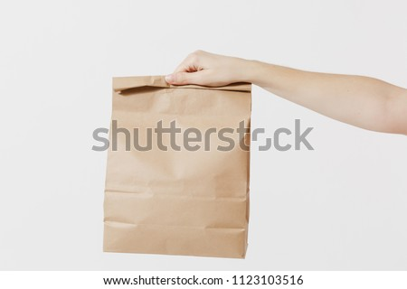 Close up female holds in hand brown clear empty blank craft paper bag for takeaway isolated on white background. Packaging template mock up. Delivery service concept. Copy space. Advertising area #1123103516