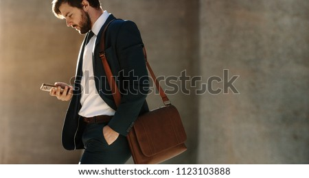 Businessman looking at his mobile phone while walking on street to office. Busy office going man commuting to office carrying his office bag and using mobile phone. #1123103888