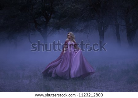 A frightened girl blonde runs away from a forest that has covered a thick fog. On the elf, a luxurious purple dress with a long train and a raincoat. Artistic photo. #1123212800