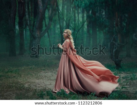 A mysterious blonde girl in a long pink dress with a train and a raincoat that flutters in the wind. The wizard leaves in a forest covered with fog. A background of trees with a haze away. Art photo #1123212806