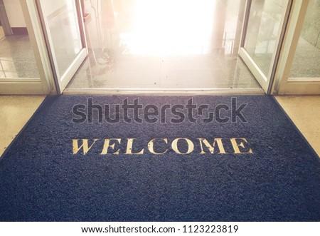 Welcome blue mat in front of door, shop