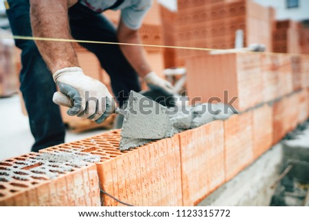 Professional worker using pan knife for building brick walls with cement and mortar #1123315772