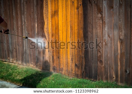 Power washing wooden fence to restore it to new. Restoration High pressure power washer spraying and cleaning wooden fence. Make old turn new. Dirty fence turned brand new again. grass and sidewalk Royalty-Free Stock Photo #1123398962