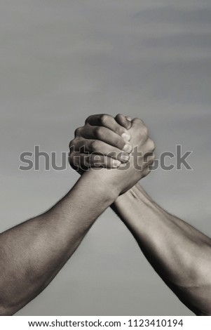 Arms wrestling, competition. Rivalry concept - close up of male arm wrestling. Leadership concept. Black and white. Rivalry, vs, challenge, strength comparison. Two men arm wrestling.
