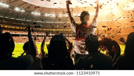 Fans celebrating the success of their favorite sports team on the stands of the professional stadium. Stadium is made in 3D. #1123410971