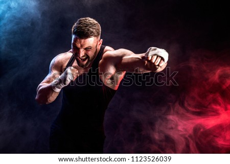 Sport concept. Sportsman muay thai boxer fighting on black background with smoke. Copy Space. Royalty-Free Stock Photo #1123526039