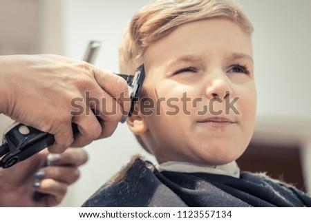 Little boy making a face while having a haircut at hair salon.  #1123557134