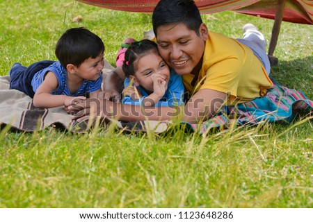 Happy latin man with his two little children having fun in the hovel made of clothing. Relaxing in the countryside. #1123648286
