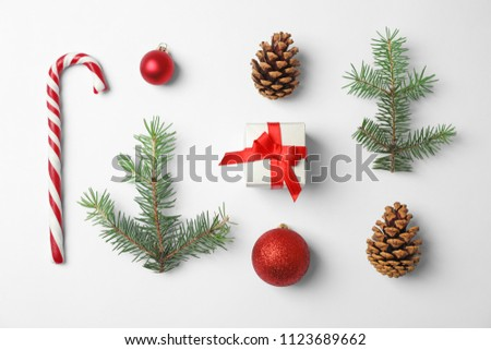 Composition with Christmas tree branches, festive decor and gift box on white background #1123689662