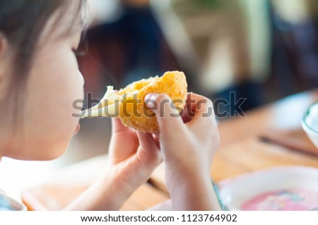 Little child asian girl eating sticky stretch fried cheese ball.Her feeling enjoyment. #1123764902
