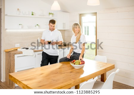 Young couple drinking coffee sitting at the table of the dining room of the modern wooden country house #1123885295