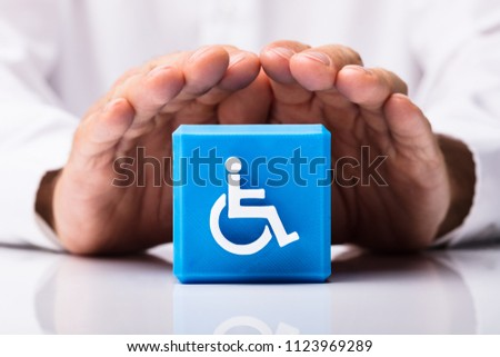 Close-up Of A Person's Hand Protecting Blue Cubic Block With Disabled Icon #1123969289