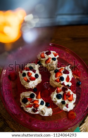 Strawberry, Blueberry and raspberry Meringue on a red crystal cake table. #1124064293
