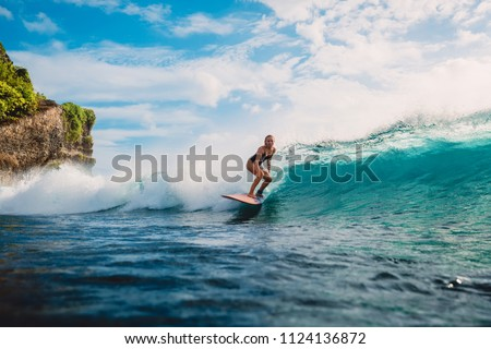 Surf girl on surfboard. Woman in ocean during surfing. Surfer and ocean wave #1124136872