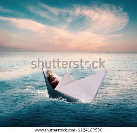 Young man taking a nap in a paper boat while sailing on the sea. #1124169536