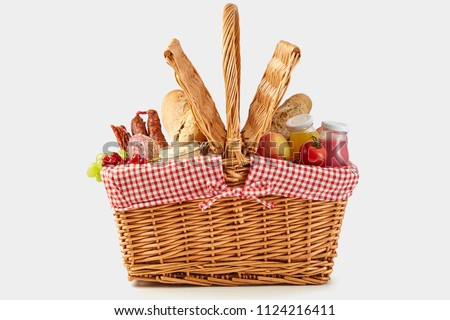 Delicious summer picnic food in a wicker hamper with crusty bread, fresh fruit and juice, cheese and tomatoes side on isolated on white #1124216411