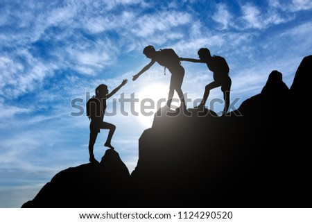 Silhouette of two female mountaineers helping another female mountaineer to overcome the obstacle in the mountains. Conceptual scene of a girl climbers #1124290520