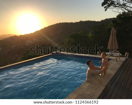 Mother playing with his daughter in the pool. Swimming pool with panoramic view at sunset in the city of Armação dos Buzios, lakes region fluminense, Rio de Janeiro, Brazil. #1124366192