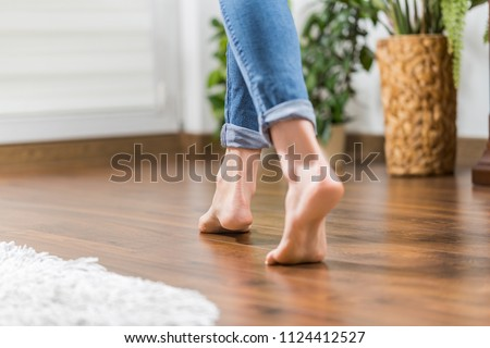 Floor heating. Young woman walking in the house on the warm floor. Gently walked the wooden panels. #1124412527
