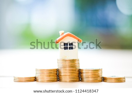 Stack of money and house model. #1124418347