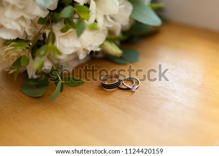 Two platinum wedding rings on wood background with flowers. Bride ring with diamonds. Shallow focus. Rustic wed concept. #1124420159