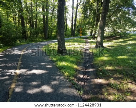 asphalt path or trail with shortcut path through the dirt and grass Royalty-Free Stock Photo #1124428931