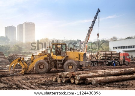 The crane is transporting wood in the sawmill #1124430896