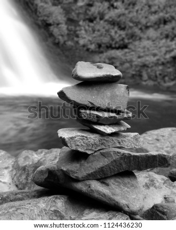 Rock stacking next to a waterfall  #1124436230