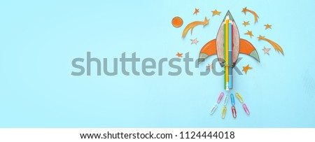 Back to school banner. rocket cut from paper and painted over wooden blue background