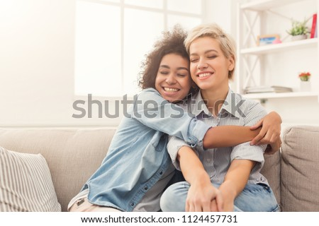 Young woman hugging her friend at home. Friends spending time together, care, friendship, fun concept, copy space Royalty-Free Stock Photo #1124457731