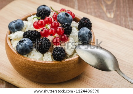 healthy breakfast: bowl of cottage cheese with fresh berries/cottage cheese with fresh berries. Selective focus #1124486390