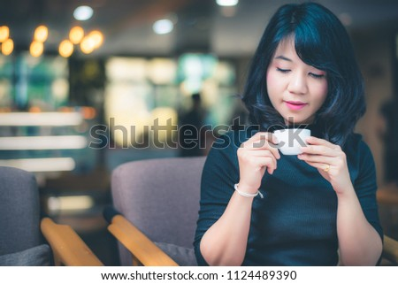 Beautiful attractive young Asian woman holding a cup of coffee in hand and sitting on sofa at cafe in the morning, vintage color tone. #1124489390