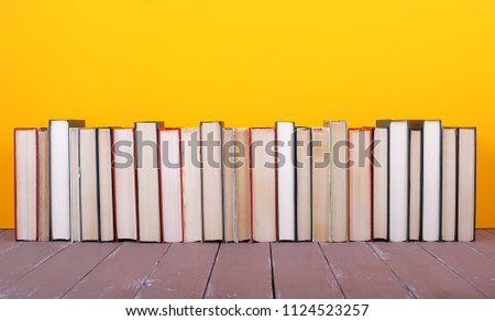 Science and education -  horizontal pile group of colorfull books on the wooden table and yellow background. #1124523257