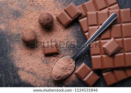 Chocolate pieces with cocoa powder in spoon on wooden table #1124531846