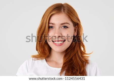 Studio shot of pleasant looking Caucasian female with gentle smile, freckled skin and make up, rejoices promotion at work, dressed in domestic clothes, isolated over white studio background. #1124556431